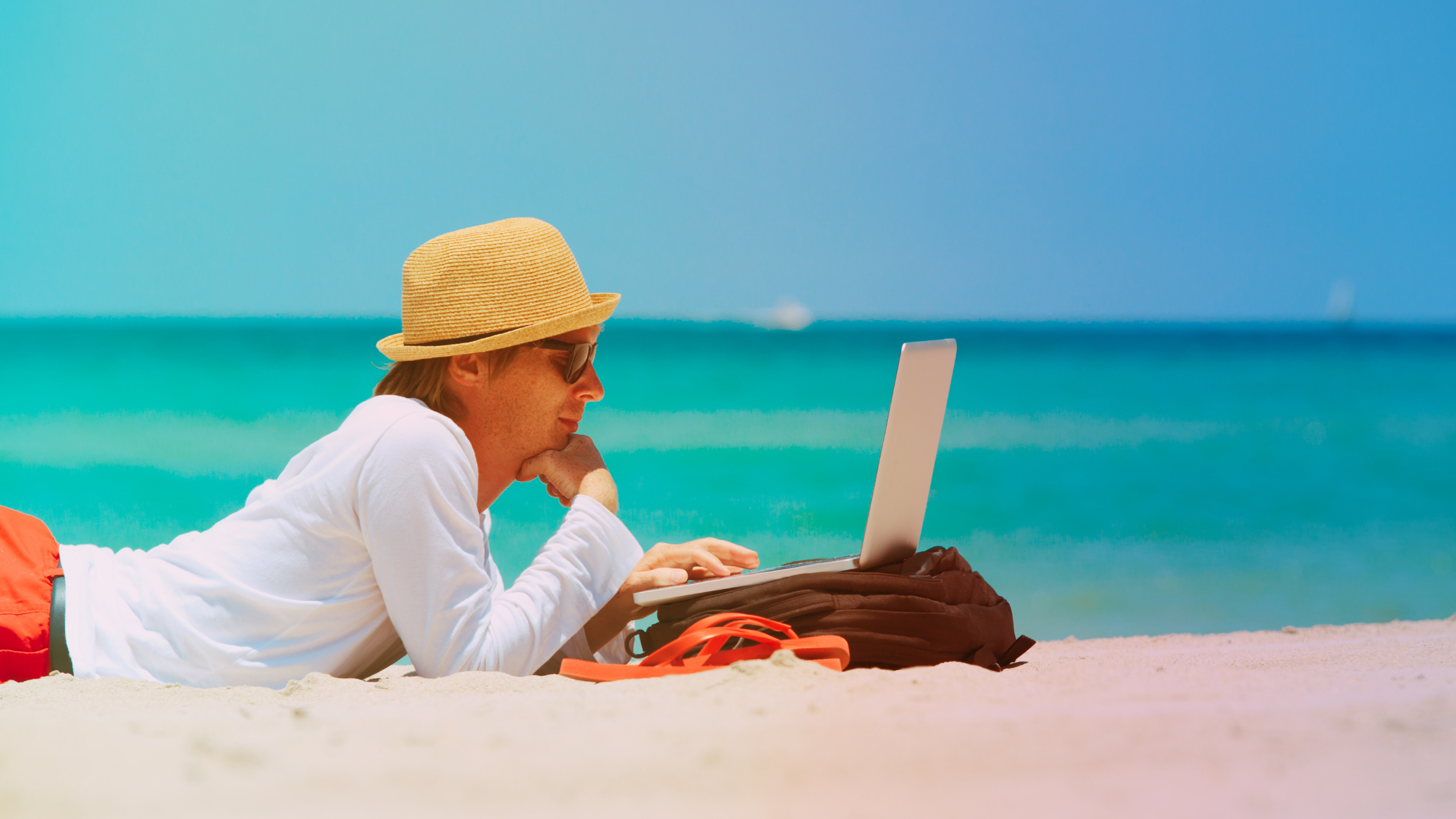 Man works remotely on laptop at the beach